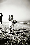little child on the beach holding a ball 1940s