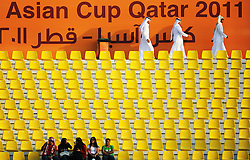 Football supporters watch the game in the Qatar Sports Club Stadium in Doha at the Asian Cup 2011