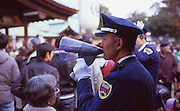 A security guard tells people not to linger in front of the crowded shrine before the beginning of the Naked Man Festival (Hadaka Matsuri) in Kounomiya, Nagoya.
