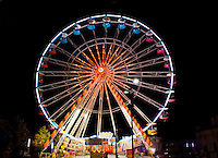 Chartres, France. Bright, colorful ferris wheel at night lighting up the sky.