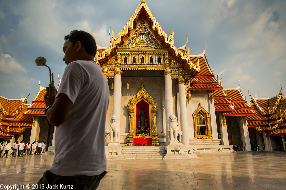 """25 FEBRUARY 2013 - BANGKOK, THAILAND:  Thai Buddhists process around Wat Benchamabophit Dusitvanaram (popularly known as either Wat Bencha or the Marble Temple) on Makha Bucha Day. Makha Bucha is a Buddhist holiday celebrated in Myanmar (Burma), Thailand, Cambodia and Laos on the full moon day of the third lunar month (February 25 in 2013). The third lunar month is known in Thai is Makha. Bucha is a Thai word meaning """"to venerate"""" or """"to honor"""". Makha Bucha Day is for the veneration of Buddha and his teachings on the full moon day of the third lunar month. Makha Bucha Day marks the day that 1,250 Arahata spontaneously came to see the Buddha. The Buddha in turn laid down the principles his teachings. In Thailand, this teaching has been dubbed the 'Heart of Buddhism'.     PHOTO BY JACK KURTZ"""
