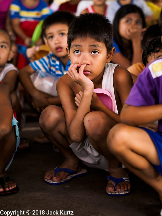 28 JANUARY 2018 - LEGAZPI, ALBAY, PHILIPPINES: Children watch a movie at the evacuation shelter for people from Barangay (community) Matanag in Albay Central School in Legazpi. People from the community have been in the shelter since Mayon volcano started erupting two weeks ago. There are about 500 families at the shelter, around 2,000 people. More than 80,000 people have been evacuated from communities around the volcano and are living in shelters and camps outside of the evacuation zone. The Philippine government is preparing to house the people for up to three months.      PHOTO BY JACK KURTZ