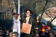 """A young woman dressed as a clown and walking on stilts carries a placard that reads """"But, here you are the clown"""" at a rally organized by il Popolo viola (The Purple People, political movement) against Prime Minister Berlusconi in Arcore, February 6, 2011. She try to see with a false telescope Villa San Martino, Berlusconi's residence in Arcore. © Carlo Cerchioli..Una giovane donna vestita da pagliaccio cammina sui trampoli con un cartello che dice """"ma, qui il pagliaccio sei tu"""" alla manifestazione organizzata da Il popolo viola contro Berlusconi ad Arcore, 6 febbraio 2011. Cerca di vedere con un falso cannocchiale Villa San Martino, la residenza di Berlusconi ad Arcore."""