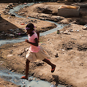 A girl crosses a ditch in Avenor, a slum in Ghana's capital, Accra. Avenor sits mere inches above the water table. According to locals, the area has experienced severe flooding since nearby bush land was cleared to create an industrial area in the 1960's. To compound the situation, poorly constructed drainage means that the drains that should carry water away from the community rather let it flow in.
