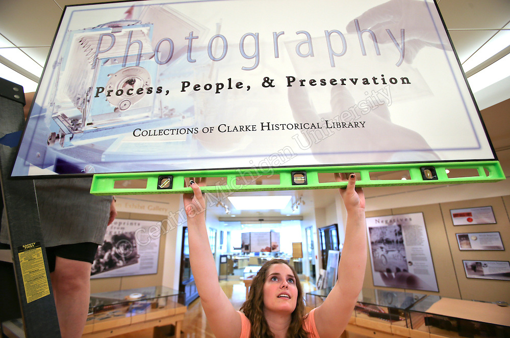 Anna Godzik, Student Worker for Exhibits Coordinator for the Park Library, Prepares the Photography- Process, People & Presentation exhibit at Clarke Historical Library which will be on display through the end of 2014. She is a minor in Museum Studies. Photo by Steve Jessmore/Central Michigan University