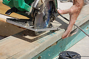 Habitat for Humanity Tucson volunteer saws lumber that will be using for framing a new house.