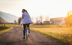 THEMENBILD - eine junge Frau fährt auf einem Damenfahrrad auf einem Feldweg bei Sonnenuntergang, aufgenommen am 18. April 2018 in Kaprun, Österreich // a young woman rides on a ladies bike on a dirt road at sunset, Kaprun, Austria on 2018/04/18. EXPA Pictures © 2018, PhotoCredit: EXPA/ JFK