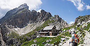 Hike to Rifugio Coldai on Monte Civetta, in the Dolomites, Belluno province, Veneto region, Italy, Europe. From Alleghe village, take a scenic lift to hikes on impressive Monte Civetta (3220 meters or 10,564 feet elevation). 200 million years ago, Triassic coral reefs fossilized into Dolomite. Collision of tectonic plates lifted the Dolomites within the Southern Limestone Alps. UNESCO honored the Dolomites as a natural World Heritage Site in 2009. This panorama was stitched from 2 overlapping photos.
