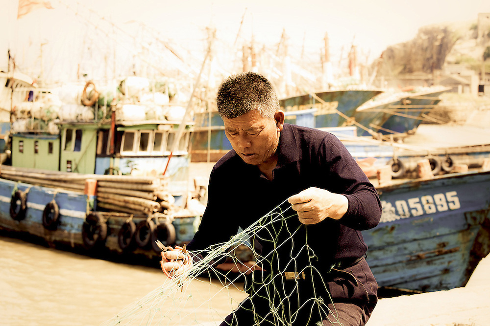 man mending fishing nets by boats,Zhoushan,China