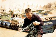 man mending fishing nets by boats,Zhoushan,China