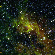 image from NASA's Spitzer Space Telescope shows a wispy, vast structure in the constellation Perseus with a small bubble right in its centre puffed out by the spasms of fresh-formed, heavyweight stars. A bubble far larger with age, down below it, has a tendril of gas sneaking across its mostly empty inner space. Along this dusty thread, stars are budding at the ends of matter columns, much like the famous 'Pillars of Creation' seen by NASA's Hubble Space Telescope in the Eagle nebula. To the middle right and out of the fray sparkles an older star cluster that has since thrown off its clouds of polycyclic aromatic hydrocarbons (PAHs), chemical compounds found in space and on Earth. Below this jewel-like collection, hydrogen atoms energized by starlight emit a rosy glow. This hue, common to many nebulae, also appears red to our eyes in visible light. The verdant PAHs signify neutral, less energized regions around this luminous hydrogen patch, and help researchers gauge the size and age of cosmic clouds.