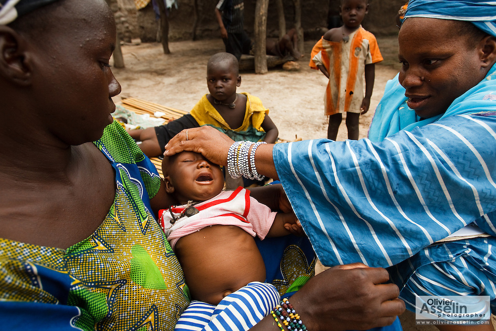 Community health volunteer Mariam Diarra examines eight-month-old Gimbala Keita, who suffers from pneumonia, during a home visit in the village of Kabe, Mali on Monday August 30, 2010..