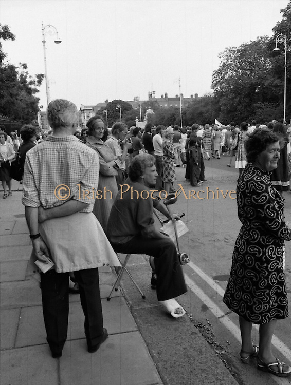 Women's Peace March In Dublin  (K50)..1976..28.08.1976..08.28.1976..28th August 1976..As part of the Peace Movement, set up by Ms Betty Williams and Ms Mairead Maguire in Northern Ireland, a march was organised for Dublin. Thousands of women took part in the march from St Stephen's Green, Dublin to the seat of government in Leinster House on Merrion Square, Dublin, to protest the continuing violence within the country..Image taken as one, less mobile,Lady takes up her vplace at parades' end in Merrion Square.
