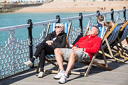 © Licensed to London News Pictures. 25/03/2017. Brighton, UK. Members of the public take advantage of the hottest day of the year to spent time sunbathing on the Brighton Palace Pier. Photo credit: Hugo Michiels/LNP