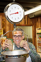 Happy mature man measuring potato in weight scale