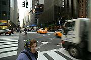 A lady waits on a crosswalk in Manhattan, New York.