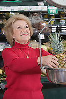 Senior woman weighing pineapple in supermarket