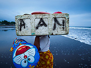 29 JULY 2017 - AIRKUNING, BALI, INDONESIA: A fisherman's wife carries supplies off of her husband's outrigger canoe after he returned from a night's fishing on the Indian Ocean in Airkuning, a Muslim fishing village on the southwest corner of Bali. Villagers said their regular catch of fish has been diminishing for several years, and that are some mornings that they come back to shore with having caught any fish.    PHOTO BY JACK KURTZ