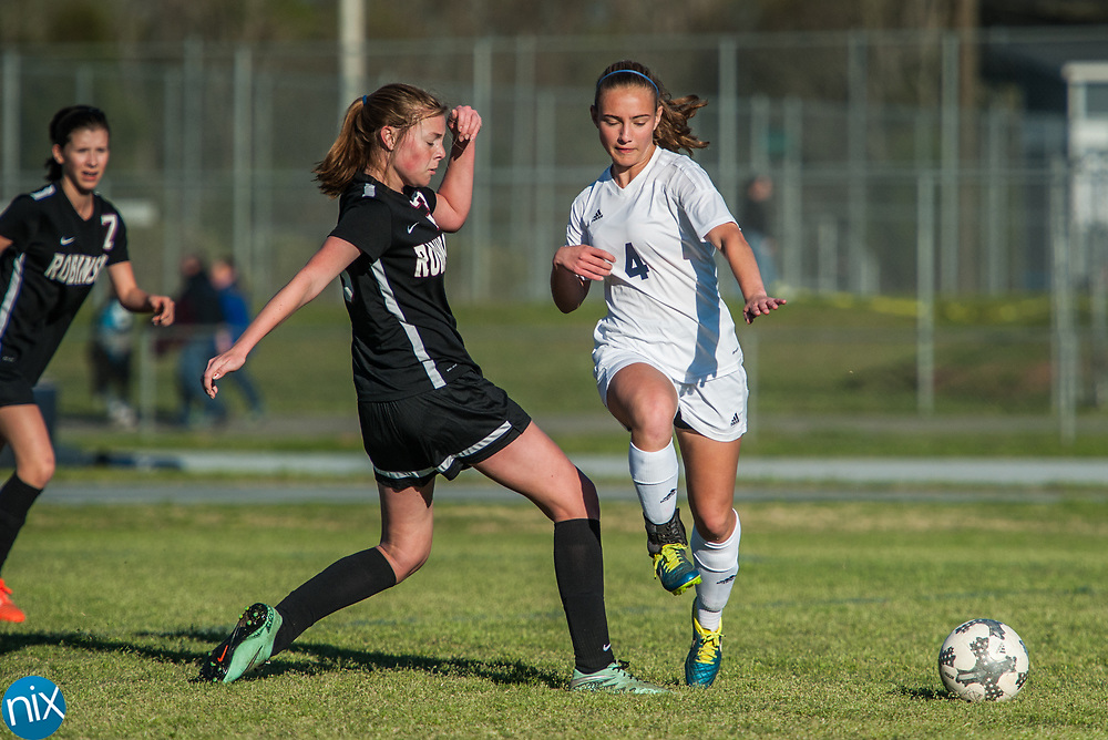 Hickory Ridge's Maddie Capel (4) and Jay M. Robinson's Marie Spokas (13) fight for the ball Friday night at Hickory Ridge High School in Harrisburg. The game ended in a 2-2 draw after double overtime.