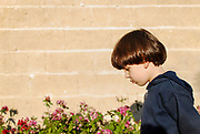 Young sad boy of six walks with his head held low in a garden