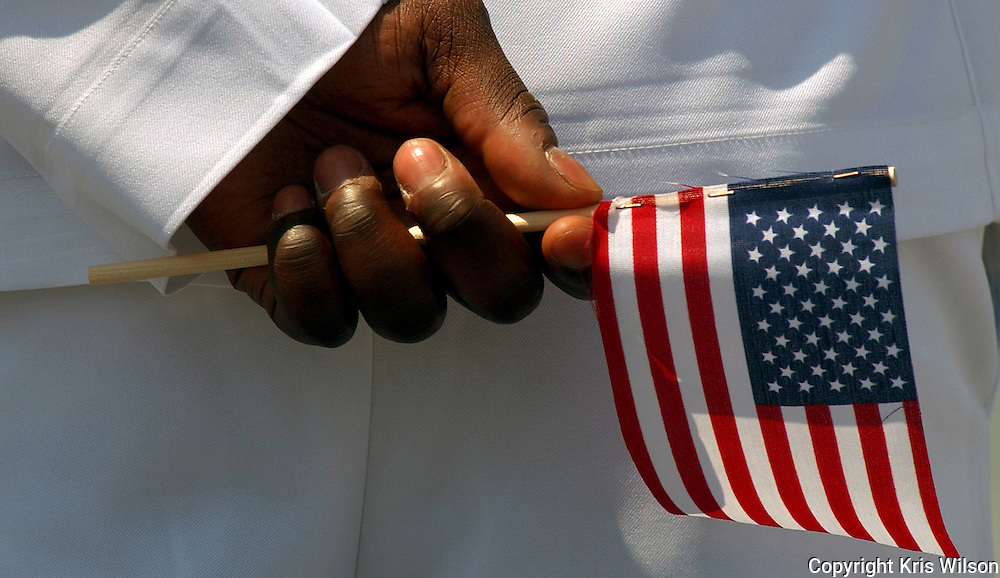 A Sailor holds an American flag in his hand while manning the rails as the Nimitz-class aircraft carrier USS Harry S. Truman (CVN 75) makes her way towards her homeport of Naval Station Norfolk after completing a six-month deployment to the Arabian Gulf in support of the Global War on Terrorism.  (Released)