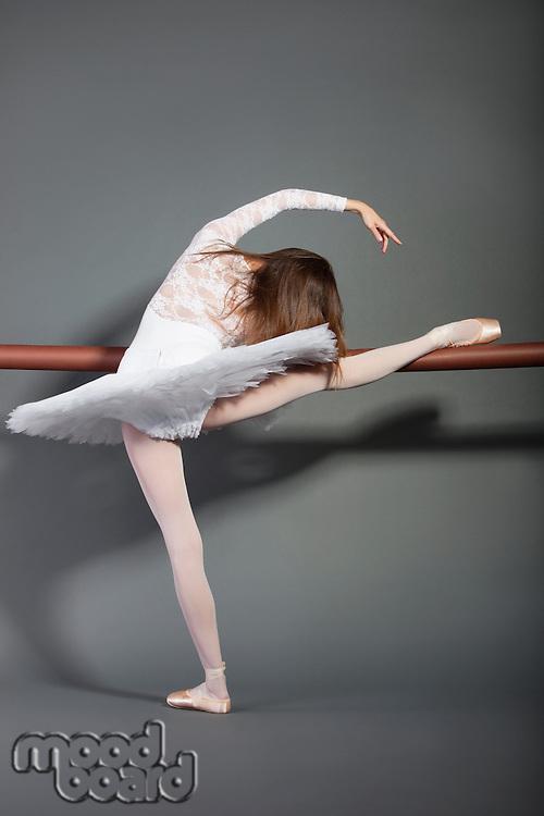 Young female ballet dancer stretching at ballet bar over grey background