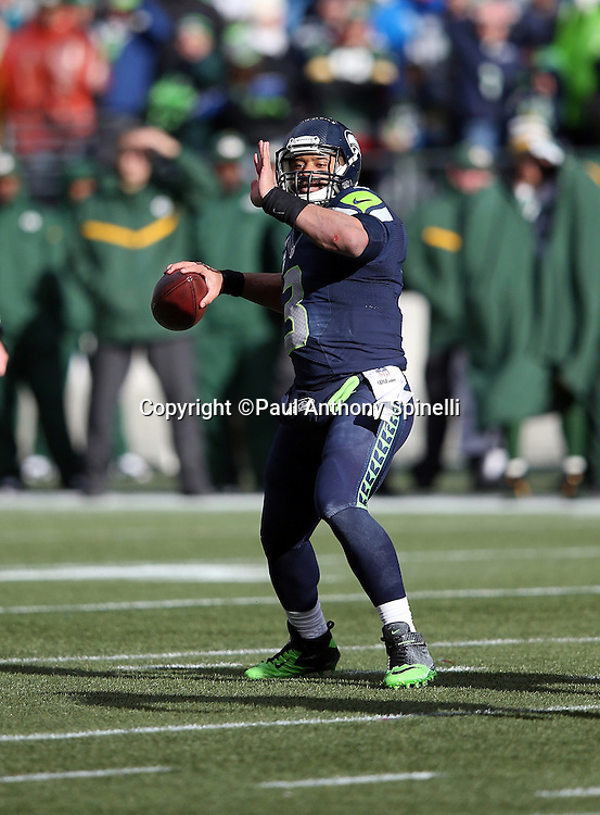 Seattle Seahawks quarterback Russell Wilson (3) throws a deep pass during the NFL week 20 NFC Championship football game against the Green Bay Packers on Sunday, Jan. 18, 2015 in Seattle. The Seahawks won the game 28-22 in overtime. ©Paul Anthony Spinelli