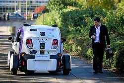 © London News Pictures. 11/10/2016. Milton Keynes, UK. A man watches a driverless car pass him by, while being tested around pedestrian areas in Milton Keynes in the first public test of autonomous electric vehicles in the UK. The vehicles have been developed by the Oxford Robotics Institute and Oxbotica. Photo credit: Ben Cawthra/LNP