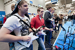 Teenagers playing electric guitars connected to Guitar hero,computer games at CeBIT 2011 digital and electronics trade fair in Hannover March 2011 Germany