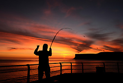 © Licensed to London News Pictures. <br /> 26/03/20167. <br /> Saltburn by the Sea, UK.  <br /> <br /> A fisherman casts from the end of the pier as a spectacular sunrise starts the day in Saltburn by the Sea.<br /> <br /> Photo credit: Ian Forsyth/LNP