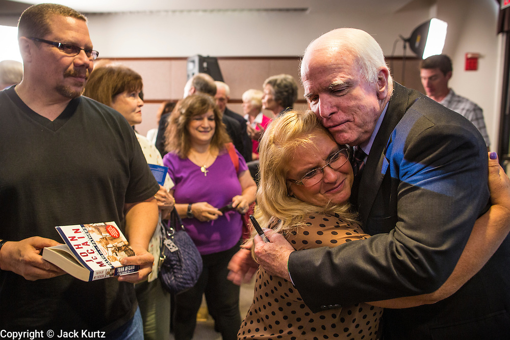 23 AUGUST 2012 - PEORIA, AZ:   Senator JOHN McCAIN (R-AZ), RIGHT, hugs DORIS GOETZ, from Goodyear, AZ, after a town hall meeting in Peoria, AZ. Sen. McCain held a town hall in Peoria, a suburb of Phoenix, to talk about the impact that sequestration would have on the Arizona economy and the Department of Defense. McCain said sequestration would immediately cost Arizona more than 35,000 defence related jobs and decimate the armed forces. Sequestration would result in about $1.2 trillion being cut from the federal budget. Sequestration, and automatic budget cuts, is scheduled to go into effect on Jan 1, 2013, if the President and Congress can't agree on budget.    PHOTO BY JACK KURTZ