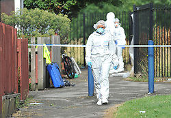 © London News Pictures. 29/07/2013. Manchester, UK. POlice forensics officers at the scene near a property on  Delta Walk, in Moston, Manchester where A father has been stabbed to death and his 13-year-old child left in a critical condition. A second man, who also suffered stab wounds,  died after he crashed a hijacked car into a nearby pub. Photo credit Steve Allen/LNP