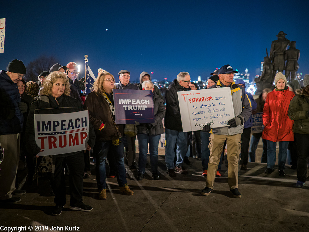17 DECEMBER 2019 - DES MOINES, IOWA: CARL SCHUMANN, from Beaverdale, IA, right, a supporter of Senator Elizabeth Warren, with a sign calling for the impeachment of President Donald Trump. About 300 people came to the Iowa State Capitol in Des Moines in near freezing weather Tuesday evening to call for Trump's impeachment. The rally, and others like it around the US, come on the eve of an impeachment vote in the US House of Representatives.   PHOTO BY JACK KURTZ