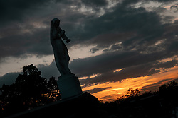"Der Metairie Cemetery ist ein ländlicher Friedhof in New Orleans, Louisiana, USA. Der Name laesst faelschlicherweise vermuten, dass sich der Friedhof in Metairie, Louisiana, befindet. Er befindet sich jedoch innerhalb der Stadtgrenzen von New Orleans an der Metairie Road. Diese Grabstaette war zuvor eine Pferderennbahn, des 1838 gegründeten Metairie Race Course. Auf der Rennstrecke fand am 1. April 1854 das berühmte Lexington-Lecomte-Rennen statt, das als ""Norden gegen den Süden"" -Rennen bezeichnet wurde. Der frühere Praesident Millard Fillmore war anwesend. Wegen des amerikanischen Bürgerkriegs wurde das Rennen eingestellt und als konfoederiertes Lager (Camp Moore) genutzt, bis David Farragut im April 1862 New Orleans für die Union einnahm. Der Metairie Cemetery wurde danach auf dem Gelände des alten Metairie Race Course errichtet. Im Bild ein Sonnenuntergang und eine Engelsstatue, aufgenommen am 15.02.2020, New Orleans, Vereinigte Staaten von Amerika // Metairie Cemetery is a rural cemetery in New Orleans, Louisiana, United States. The name has caused some people to mistakenly presume that the cemetery is located in Metairie, Louisiana; but it is located within the New Orleans city limits, on Metairie Road (and formerly on the banks of the since filled-in Bayou Metairie). This site was previously a horse racing track, Metairie Race Course, founded in 1838. The race track was the site of the famous Lexington-Lecomte Race, April 1, 1854, billed as the ""North against the South"" race. Former President Millard Fillmore attended. While racing was suspended because of the American Civil War, it was used as a Confederate Camp (Camp Moore) until David Farragut took New Orleans for the Union in April 1862. Metairie Cemetery was built upon the grounds of the old Metairie Race Course after it went bankrupt. The race track, which was owned by the Metairie Jockey Club, refused membership to Charles T. Howard, a local resident who had gained his wealth by starting the fi"
