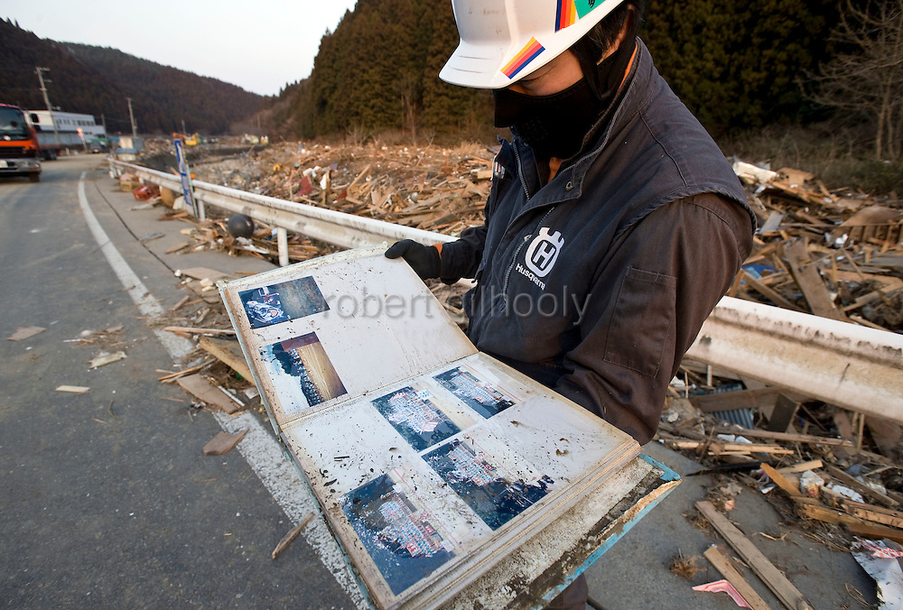 A man finds a photo album among the ruble after a massive tsunami that followed the March 11 magnitude 9 quake swept through the coastal town of Minami Sanriku, Miyagi Prefecture on 13 March, 2011.  Some 10,000 people of the town's 17,000 population are either dead or missing. Photographer: Robert Gilhooly