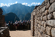 A group of tourists looks towards the Andes mountains from one of the terraces of Machu Picchu in Peru.  The site draws up to 2,500 visitors a day, who can either walk up from Aguas Calientes, take a harrowing switchback bus ride, or arrive via one of the ancient trails through the mountains.
