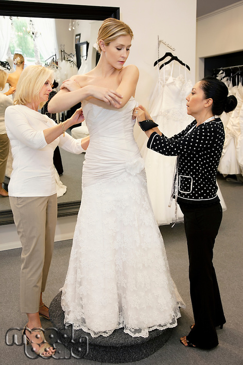 Mother and store employee assisting young woman getting dressed in bridal store