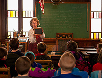 Kathy Lacroix describes school days during colonial times to 4th grades from Gilford Elementary School during thier Thompson-Ames Historical Society walking field trip on Thursday morning.  (Karen Bobotas/for the Laconia Daily Sun)