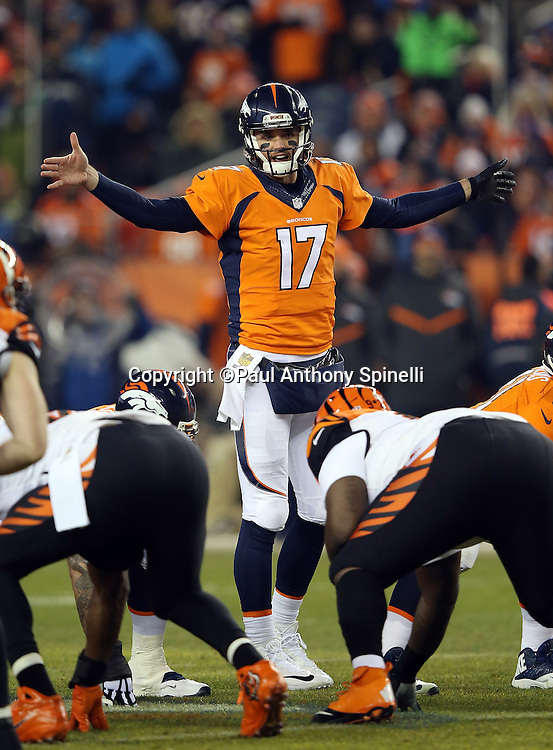 Denver Broncos quarterback Brock Osweiler (17) waves his arms as he calls a play over center during the 2015 NFL week 16 regular season football game against the Cincinnati Bengals on Monday, Dec. 28, 2015 in Denver. The Broncos won the game in overtime 20-17. (©Paul Anthony Spinelli)