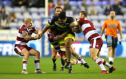Wigan Warriors' Gabriel Hamlin (left) and Tony Club (right) tackle Wakefield Trinity's Pauli Pauli during the Betfred Super League Super 8's match at the DW Stadium, Wigan.