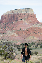 All American good looking cowboy with an open shirt on a rugged mountain top ranch
