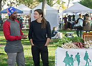 mkb102117b/metro/Marla Brose -- At the Downtown Growers' Market, Abedi Mlondani, left, a resettling refugee originally from the Democratic Republic of Congo (DRC), chats with Zoey Fink, program coordinator for the Refugee Agricultural Partnership Program and farm manager at Tres Hermanas Farm, a gardening program for Albuquerque refugees through the Lutheran Family Services, Saturday, Oct. 21, 2017, in Albuquerque, N.M. Resettling refugees were learning to sell their produce at the market. This season Tres Hermanas Farm has had their produce at the Nob Hill Growers' Market on Thursday afternoons.  When the growers' markets close Tres Hermanas produce will be sold to restaurants and other businesses. (Marla Brose/Albuquerque Journal)