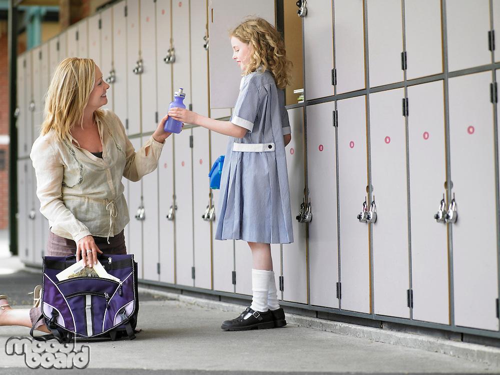 Mother packing daughters school bag near school lockers