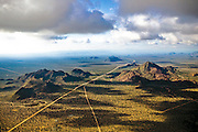 Scattered clouds cast shadows over northwestern Arizona scrub desert. Moisture passes over the dry land below, leaving the area's average rainfall at a meager 7.5 inches per year.