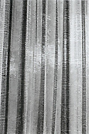 Abstract shot of mesh curtains in a vertical drape pattern.