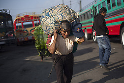 59593051 .A man carries merchandise at the La Terminal market on the International Labour Day, in Guatemala City, capital of Guatemala, on May 1, 2013. According to local media, the labour conditions and the lack of economic stability in Guatemala forces the population to migrate to the U.S. in search of better work conditions, on May 1, 2013, May 2, 2013 Photo by: i-Images.UK ONLY