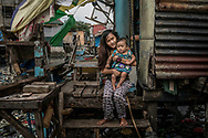 """Jasmin Dorana, a 15 year old widow, holds her baby, Hazel, born just a month before her partner, John """"Toto"""" Dela Cruz was pulled by his hair out onto this porch and shot four times in the head and in the chest.  Bagung Bayan, C4, Navotas, Metro Manila, Philippines."""