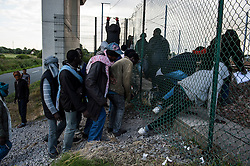 © London News Pictures. Calais, France. A group of african immigrants gain access to the Eurotunnel tracks by crawling underneath a gap in a fence. Migrants attempting to reach the UK via the Eurotunnel at Calais in France. The situation has reached crisis point, which French police over run by attempts to cross the border. Photo credit: Ben Cawthra /LNP