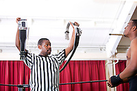 Referee showing champion belt while looking at wrestler in ring