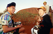 Ayers Rock (Uluru). Japanese tourist having bento breakfast while waiting for sunrise.